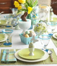Blue & Green Easter Tablescape--chocolate rabbit nestled in edible grass in a milk glass compote; blue ceramic fruit basket holding pastel speckled eggs; bamboo placemats; and handmade egg place card holders.
