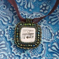 Ceramic button – a vintage ceramic button with musical notes makes for a wonderful focal point of this hand-embroidered pendant. I further embellished it with a bezel of shiny green beads, green faceted glass beads and picots of copper-green beads. The pendant measures 38x43 mm and comes with a brown ribbon necklace. Available from www.jessicagrimm.com