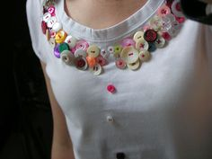 Colorful buttons sewed around the neck of a tee Shirt. (Real Pretty)
