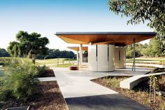 Overview of the kiosk and toilet pavilions, each sheltering under a folded ply roof responding to the rolling hill landscape by JMD Design.