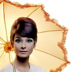A publicity photo of Audrey Hepburn posing with a yellow parasol for the movieHow to Steal a Million. Photograph byDouglasKirkland at theStudio de Boulogne. Paris, France, November 1965.
