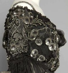 BLACK CHIFFON & SEQUIN BALLGOWN, c. 1905. 2-piece, black chiffon over black silk, trimmed in nipple shaped ombre gray sequins & lattice pattern cut steel beads, off the shoulder bodice w/ narrow shoulder straps, chiffon flounced sleeves, trained skirt. Detail