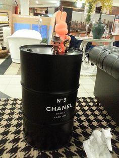 Tambor de metal com a marca da grife Chanel, com bonecos de Toy art.
