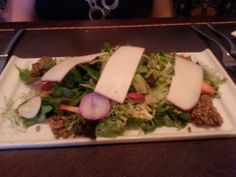 Mixed green salad topped with sliced manchego cheese, sunflower seed granola, fresh fruit, and ice wine vinaigrette at Disney World's Artist Point restaurant.