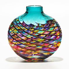 Michael Trimpol     Blown Glass with a multicolored, swirled, swagged and twisted pattern. Flattened profile fits neatly on narrow surfaces. Size and color will vary slightly. Signed on bottom.