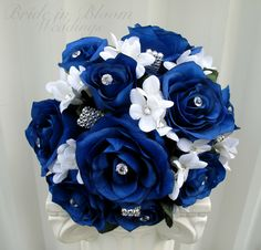 "A wedding bouquet of class and elegance. This bouquet is designed with 10 royal blue roses, white gem stephanotis, with rhinestone bling throughout the bouquet. Handle treatment is wrapped with a white lace shimmer ribbon, finished with a rhinestone band & sparkling broach buckle. Bouquet measures 8"" ( 20 cm ) wide x 12"" ( 30 cm ) tall."