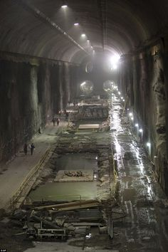 Future gateway: New York construction workers are seen dwarfed by four tunnels easily seen running into the city's future concourse that is about five-football fields long and eight-stories high: