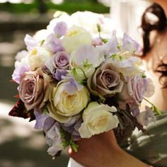 Gorgeous hand-tied wedding bouquet designed with white and lilac roses and sweetpeas.