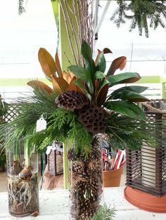 Rustic Christmas vase with magnolia, birch, lotus and evergreens. Fill the glass vase with pine cones to hide your stems