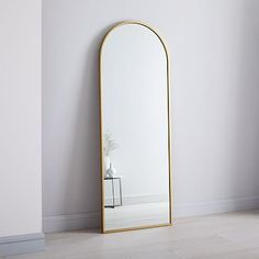 """Our best-selling Metal Framed Floor Mirror gets an update with an arched silhouette that looks elegant in an entryway, living room or bedroom. • 28""""w x 1.3""""d x 74""""h. • Mirrored glass. • Metal frame in an Antique Brass finish…"""