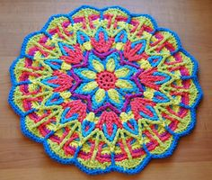 Looks too large to be a potholder, but you could stop partway with the blue and green serrated edge.  Overlay Crochet Mandala