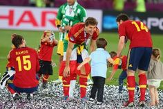 KIEV, UKRAINE - JULY 01: The players' children play in the confetti with (L-R) Sergio Ramos, Fernando Llorente and Xabi Alonso of Spain after the UEFA EURO 2012 final match between Spain and Italy at the Olympic Stadium on July 1, 2012 in Kiev, Ukraine.