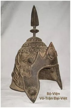 helmet under Tran dynasty from to century with many forms like Đâu-Mâu 兜 鍪 or Khôi-Mạo 盔 帽 is holding a pointed high crest with plume , or Phượng-Dực Mạo 鳳 翊 帽. Warrior Costume, Arm Armor, Body Armor, Vietnam History, 15th Century, Decorative Bells, Mystery, Bronze, Costumes