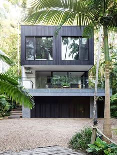Nestled into rainforest on the edge of a national park in Noosa, on Queensland's Sunshine Coast, a dated 1980s holiday home has been given a refreshing makeover by Melbourne interior design firm, Mim Design.