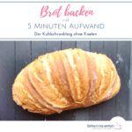 Langes Brot auf dunklem Untergrund mit Mehlspuren. Aufschrift sagt: Brot backen mit 5 Minuten Aufwand - Der Kühlschrankteig ohne Kneten.