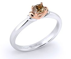 18K gold ring with a cushion-cut cognac diamond (3.45x3.25mm; 0.27ct) resting into a pink gold heart. Available size: 50 • Breathtaking design • Magical details • Authentic diamond, ruby, emerald, sapphire rings