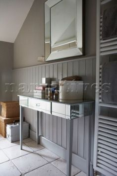 Bathroom close up with tongue and groove panelling and mirrored furniture beside modern towel radiat