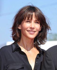 La frange ajoutée de Sophie MarceauSophie Marceau affiche un carré mi-long et une frange ajourée. Une coiffure qui permet de dissimuler les rides tout en accentuant le regard. La longueur, quant à elle, rajeunit l'ensemble tout en mettant en valeur les pommettes de l'actrice.