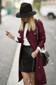 Fierce in a burgundy trench coat, black leather skirt and stylish hat.