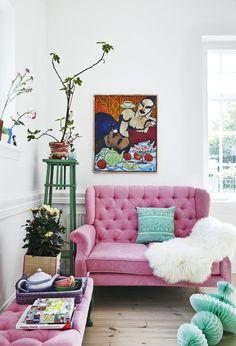 Nieco teatralna stylistyka tego kącika wypoczynkowego z pikowaną różową sofą zdecydowanie przyciąga wzrok. Nad meblem zawieszono wyraziste malowidło w stylu nawiązującym do ekspresjonizmu. Kwietnik urozmaica kolorystykę wystroju swoim zielonym kolorem.
