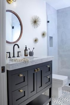 Black-and-white tiles in a graphic pattern create style underfoot in this contemporary bathroom. The sleek black vanity topped with cool gray countertops features open and closed storage, while starburst decorations add a touch of whimsy to the space.