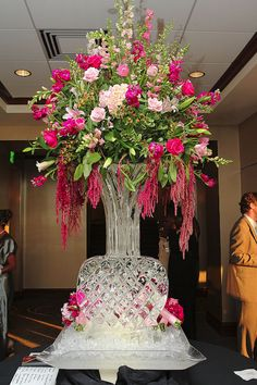 TOTALLY LOVE THIS ICE VASE WITH HANGING AMARANTHUS, LARKSPUR (NOT FOND OF) SNAP DRAGONS, ACAPULCO LILLIES, FUSCHIA STOCK, PINK TULIPS, PINK HYDRANGEAS, COFFE BERRIES, AND PINK AND FUSCHIA ROSES.