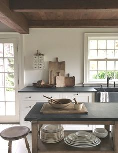 Beautiful and understated cream/ivory kitchen with open, stained island, rustic ceiling, and soapstone counters. Wish I knew the source!