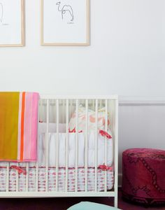 A white crib with pink-and-white bedding and a striped blanket.