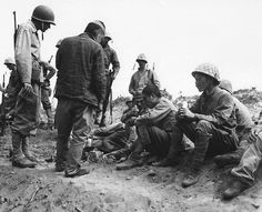 Soldados US comparten sus raciones con los prisioneros japoneses, Iwo Jima, 1945.