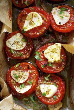 Halveer de tomaten,besprenkel ze met peper,zout,tijm,oregano,basilicum,leg op elke halve tomaat een plakje knoflook.druppel er tot slot olijfolie over.zet ze 1 uur in de oven op 160*.