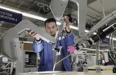 David Mendiola adjusts the arms of a da Vinci Surgical System as he conducts a system integration test at the headquarters and manufacturing plant of Intuitive Surgical in Sunnyvale, Calif. on Friday, Aug.10, 2012.