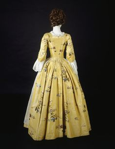 Silk and linen dress, back view. Dress with closed robe, sleeves pleated at the elbow. Its bodice is lined in coarse linen and boned on either side of its front opening with fastening eyelets concealed behind robings. Yellow silk taffeta, probably a lustring, brocaded with coloured silks with some details self-coloured, formed by an interrruption of the ground weave. The flowers are treated naturalistically, typical for this period. The design has a drop reverse repeat. At the
