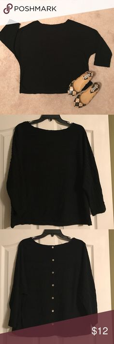 Black top button up the back This soft polyester and rayon top has a raised line pattern across the body and sleeves. The unique feature is the button up back. Investments Tops Blouses