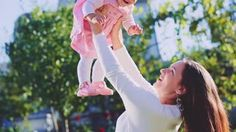 Mother is playing with her baby daughter outdoors. Slow Motion 250 fps. Young…