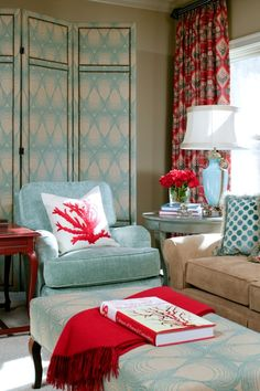 Just a punch of coral gives this red and turquoise room design an aquatic feel! Design by Tobi Fairley