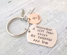 This is a personalized handstamped Godmother/Godfather Keychain gift. The aluminum 1 1/2 inch dog tag has Godmother, A gift from above for guidance and love stamped in posh font. You can change this to Godfather. This also has a 3/4 of an inch copper disc with a name and a cross