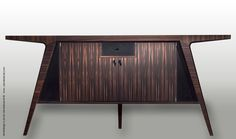 SWITZER CULT CREATIVE Model 2701: Sideboard Sideboard with three legs and pull out drawer in leather.  Shown in Macassar Ebony.  78 3/4″ x 19 3/4″ x 35 1/2″ High. Find this and many more beautiful pieces from Ernest Gaspard & Associates