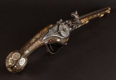 A long wheel lock petronel or holster pistol in the Dresden style. The Pistol with a fruitwood stock inlaid with mother of pearl and horn plaques of grotesques and animals ending in a fluted pear-shaped pommel with an iron trigger-guard and the ramrod-pipes and fore-end cap each of engraved horn (ramrod and some mother of pearl and ivory replaced). Most likely German.