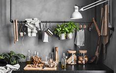 Rail réalisé avec de vieux tuyaux, servant de rangement à des ustensiles de cuisine et à des objets décoratifs, au-dessus d'un plan de travail avec bocaux en verre