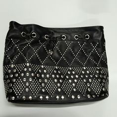 Black Leather & Silver Studded Shoulder Purse Stylish and efficient, bucket shaped, black leather purse. The studs are circular, and are in diamond and triangle shaped designs. The top has a magnetic closure and studded holes along the top which are capped with silver bullets, where the thick leather shoulder straps link. Back side has a zipper pocket with beige lining and the other has one zippered  pocket and two open pockets. This is brand new and in perfect condition! Big enough to fit a…
