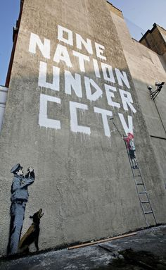 New Banksy Painting Found In Central London LONDON - APRIL 14: A new Banksy graffiti work on a private property catches the eye of passers by on April 14, 2008 in London, England. The work, which depicts a child painting the words 'One Nation Under CCTV' with a security guard watching him is situated under a security camera and has appeared sometime between the hours of Saturday and Monday morning. (Photo by Cate Gillon/Getty Images)