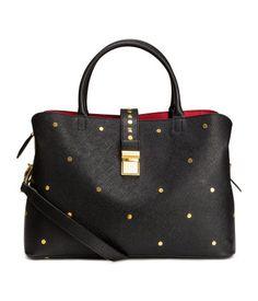 Schwarz/Goldfarben. Handtasche aus geprägtem Lederimitat mit dekorativen Metallnieten. Modell mit zwei Tragegriffen und abnehmbarem Schulterriemen.