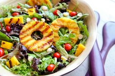 This fresh and colorful salad celebrates the grill and  Dole pineapple.  Grilled tropical fruit is tossed with greens, cherry tomatoes, and balsamic vinaigrette.   Throw in a few macadamia nuts for a bit of extra crunch.