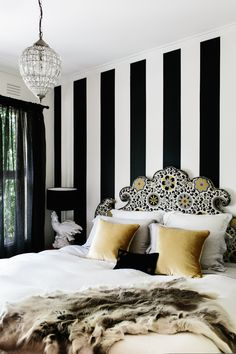 I really like this ultra curvy headboard and how the fabric pattern fits it! The black & white striped wall is the perfect backdrop too.