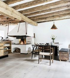 Rustic dining area with eclectic chairs and an open fireplace