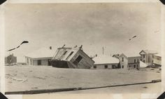 Cluster of houses submerged in sand. Wrecked houses submerged in sand on the east end of Galveston on Seawall Boulevard. One house has been turned upside down by the hurricane. Galveston 1915 Hurricane Photographs, 1915. Special Collections, University of Houston Libraries (Public Domain).