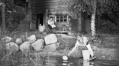 Kansallispukuiset naiset lämmittävät hirsisaunaa ja tekevät vastoja vuonna 1953. Copyright: Lehtikuva.
