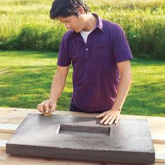 Mark Powers runs a scrap block of wood over hypertufa tabletop to soften rough spots and scrape away leftover foam