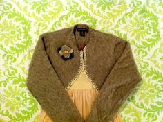 """<p>This adorable bolero-style felted shrug began its life as one of my husband's cashmere-wool sweaters. After an unfortunate run-in with a naughty moth, it ended up in my recycle pile. Since the moth holes were mostly in the body of the sweater, I though I could leave most of the …</p><div style=""""padding-bottom:20px; padding-top:10px;"""" ><!-- Hupso Share Buttons - http://www.hupso.com/share/ --><a class=""""hupso_counters"""" href=""""http://www.hupso.com/share/""""><img ..."""