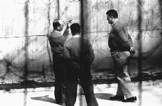 """Eichmann in Jerusalem. Caption from LIFE: """"Trying to talk during daily outdoor exercise period, prisoner Eichmann meets unshakeable stony silence from prison guards. He was allowed to walk outside for half hour a day, when weather was good."""""""